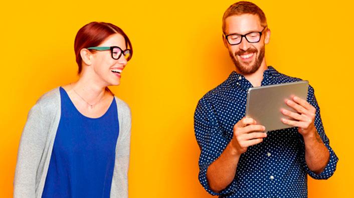 Dos jóvenes revisando una tablet. Hay que revisarse la vista una vez al año ahora que varían los hábitos.